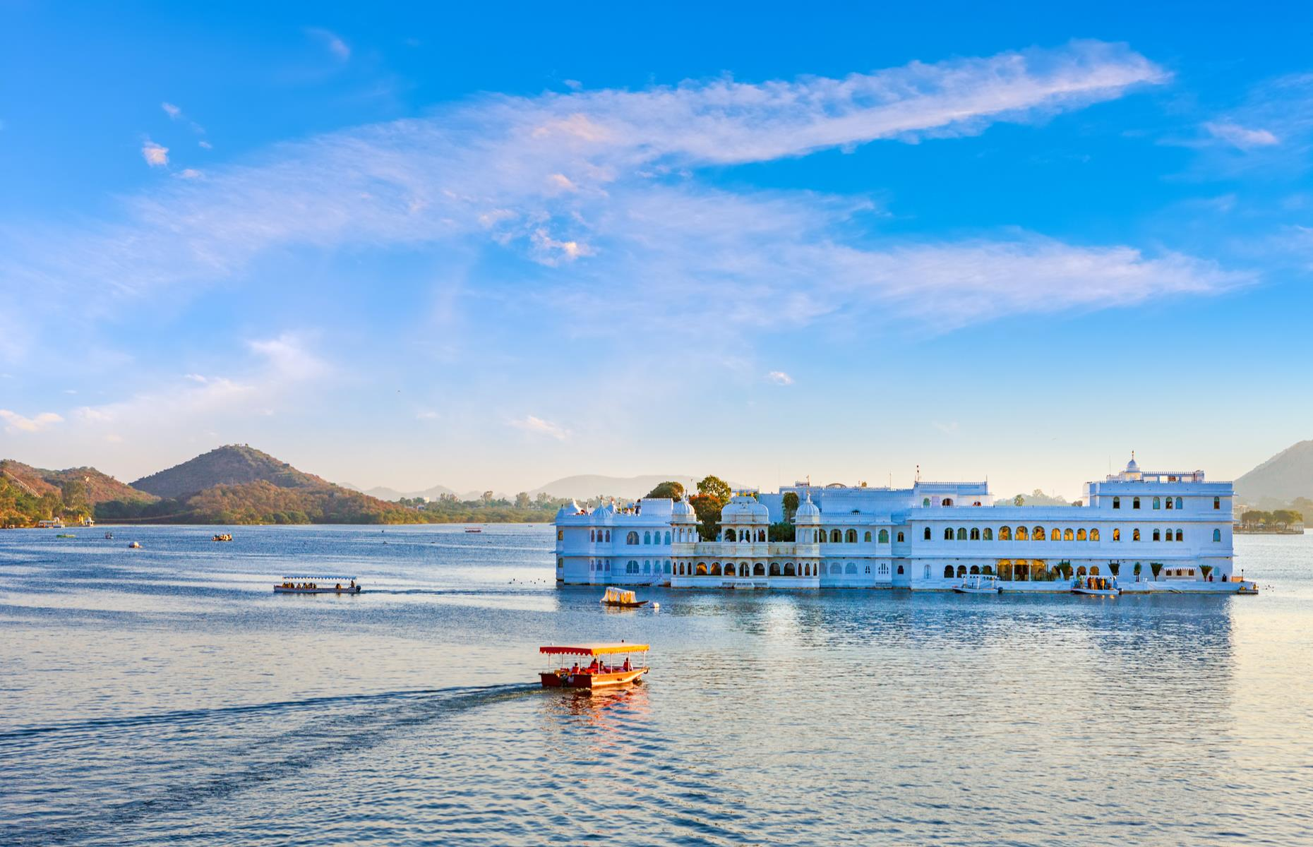 Slide 25 of 31: Dreamy Lake Pichola sits alongside the city of Udaipur in Rajasthan. It was created in 1362 so merchants could transport grain and was later enlarged by Maharana Udai Singh, who built his royal palaces and temples on the water's edge. The luxurious Taj Lake Palace (pictured), set on Jag Island in the heart of the lake, is the most famous sight. It was also one of the locations featured in the 1983 James Bond film Octopussy.