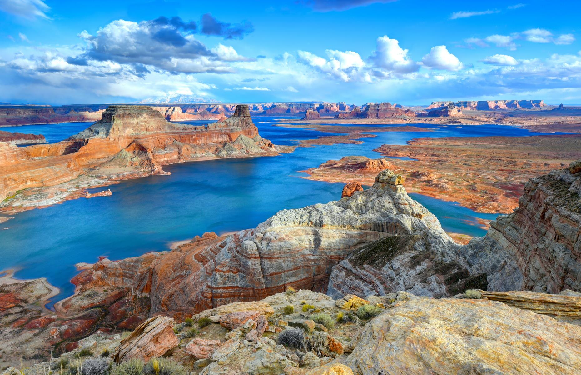 "Slide 2 of 31: When it comes to beautiful ""fake lakes"", Lake Powell, which straddles the states of Utah and Arizona, takes some beating. With its vast blue waters, natural bridges, dams and canyons carved into red and apricot rock, it's an extraordinary place. The lake was created in 1963 when the Glen Canyon Dam was built across the Colorado River. It's America's second-largest man-made lake and the most famous feature is Rainbow Bridge, the world's largest natural stone bridge."
