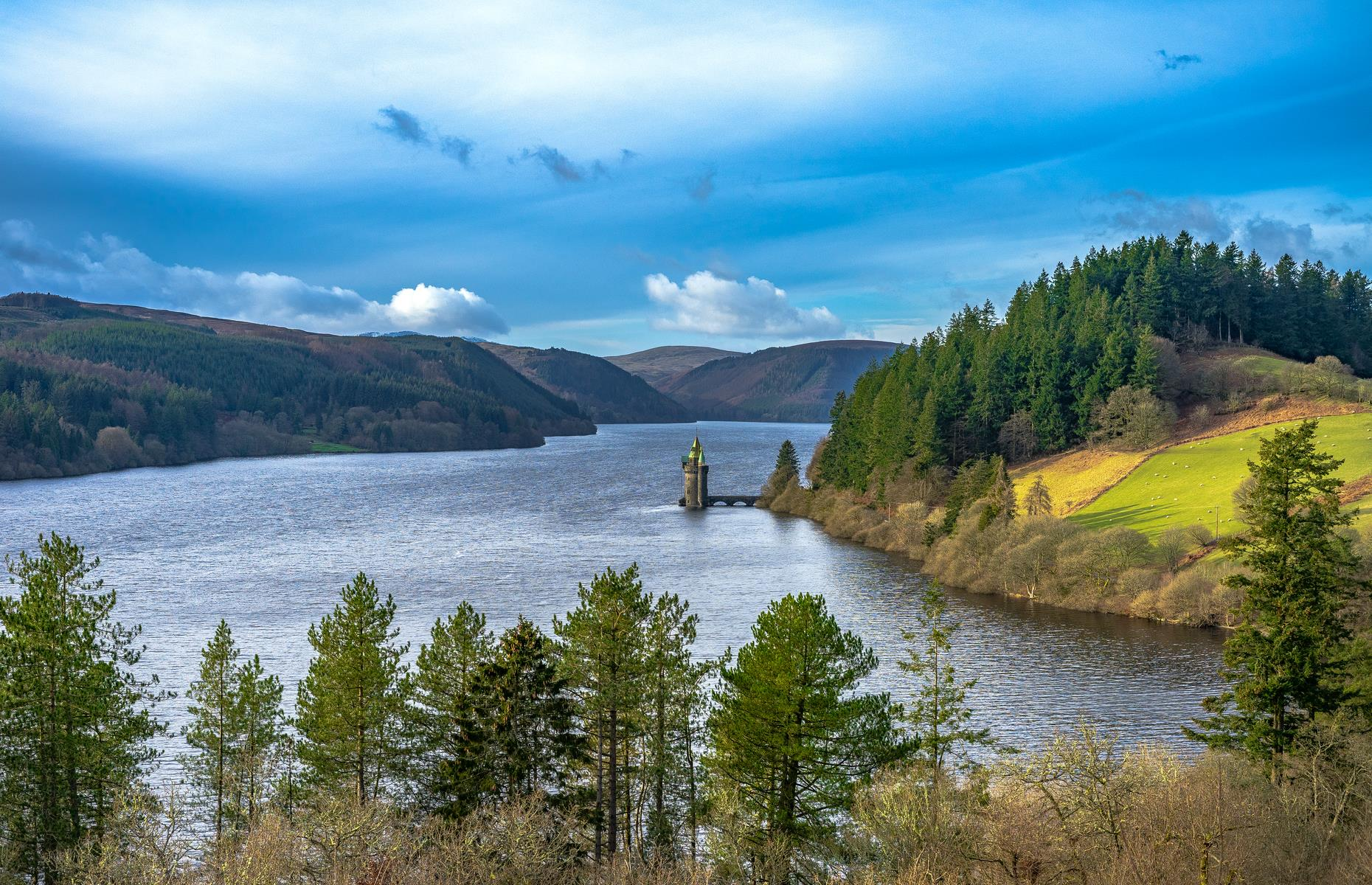 Slide 30 of 31: With its fairy tale-esque water tower and brooding mountainous surrounds, Lake Vyrnwy in Powys, Wales, is a dreamy spot. It's hard to believe that the stretch of water isn't natural, but the lake was created in the late 19th century to provide safe water to the rapidly growing city of Liverpool. The impressive stone dam that stretches across the Vyrnwy river valley was completed in 1889 – it was the first large stone-built dam in Britain. It flooded the old village of Llanwddyn, the remains of which can sometimes be seen when water levels are low. Check out more reasons to love Wales.