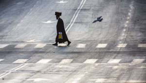 An Ultra-Orthodox Jew crosses an empty street during the first day of a three-week lockdown in Bnei Brak, Israel, Friday, Sept. 18, 2020. Israel went back into a full lockdown on Friday to try to contain a coronavirus outbreak that has steadily worsened for months as its government has been plagued by indecision and infighting. (AP Photo/Ariel Schalit)