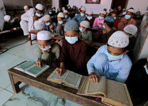 Children wearing face masks to prevent the spread of coronavirus read the Quran at a   religious school in a mosque, in Karachi, Pakistan, Saturday, Sept. 19, 2020. (AP Photo/Fareed Khan)
