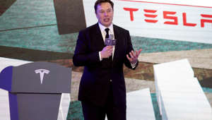 Elon Musk wearing a suit and tie standing in front of a building: Tesla CEO Elon Musk speaks at an opening ceremony for Tesla China-made Model Y program in Shanghai on Jan. 7.