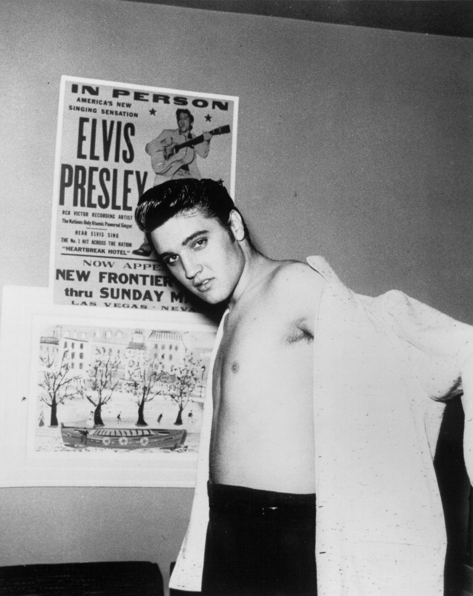 Slide 21 of 50: Elvis Presley in front of a concert poster at the New Frontier Hotel. The resort hosted Presley's first Vegas appearance in 1956.
