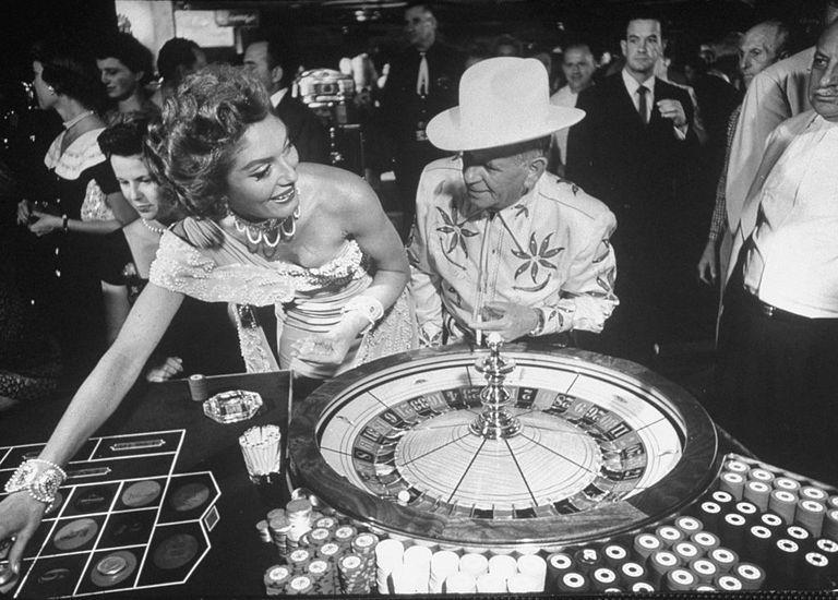 Slide 38 of 50: Jake Freedman, the owner of the Sands hotel, at a roulette table. He was often seen wearing matching cowboy-inspired outfits with his wife, Carolyn, because, why not?