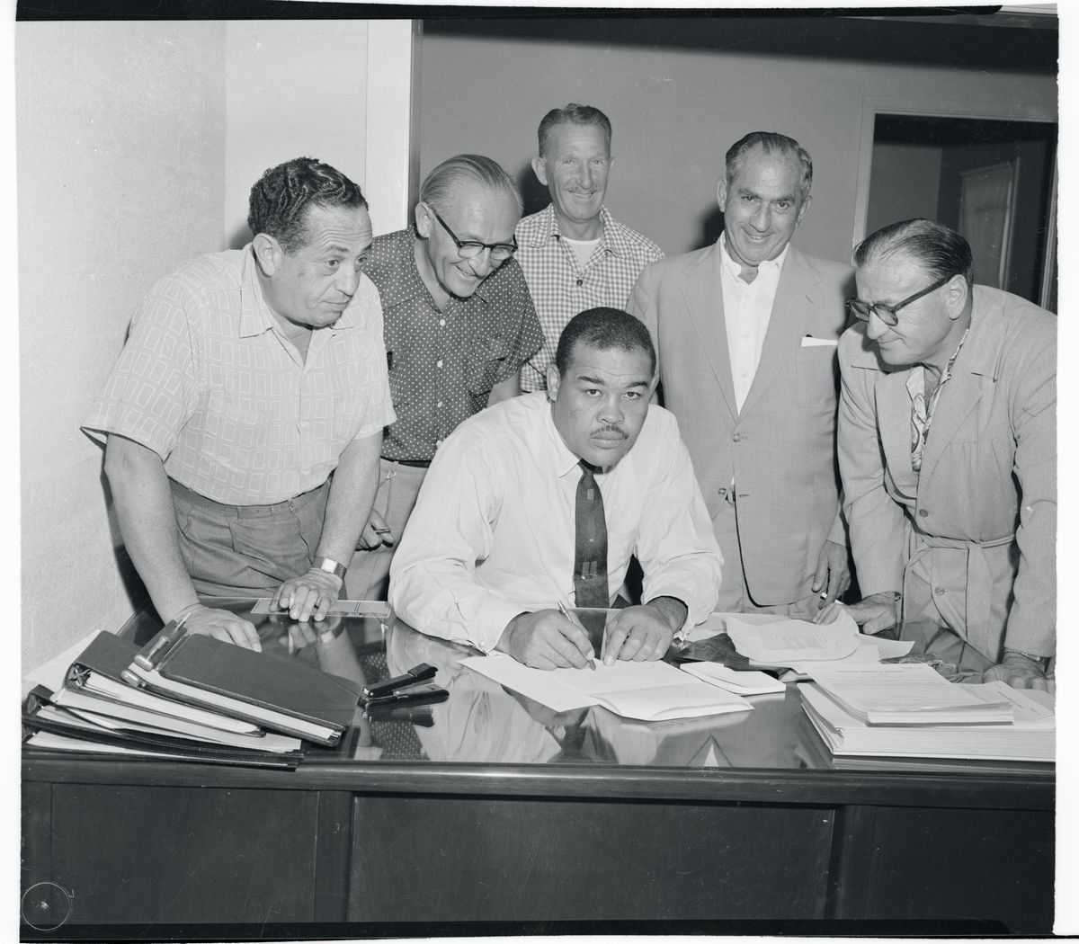 Slide 8 of 50: Former heavyweight champion Joe Louis signs a contract purchasing part interest in Las Vegas's $3,000,000 Moulin Rouge Hotel in 1954.