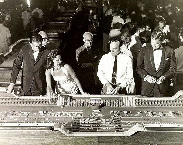 Slide 33 of 50: A 1959 photoshoot at the Sands hotel around a casino craps table.