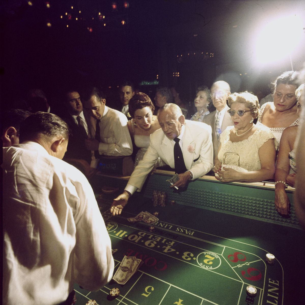Slide 7 of 50: Hotel owner Jake Freedman rolls dice at a craps table at the Dunes in 1955. The casino closed one year after Freedman bought it.