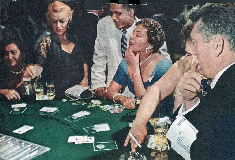 Slide 36 of 50: Patrons trying their luck at the blackjack table in the Moulin Rouge casino. Sadly, the casino closed in 1955.