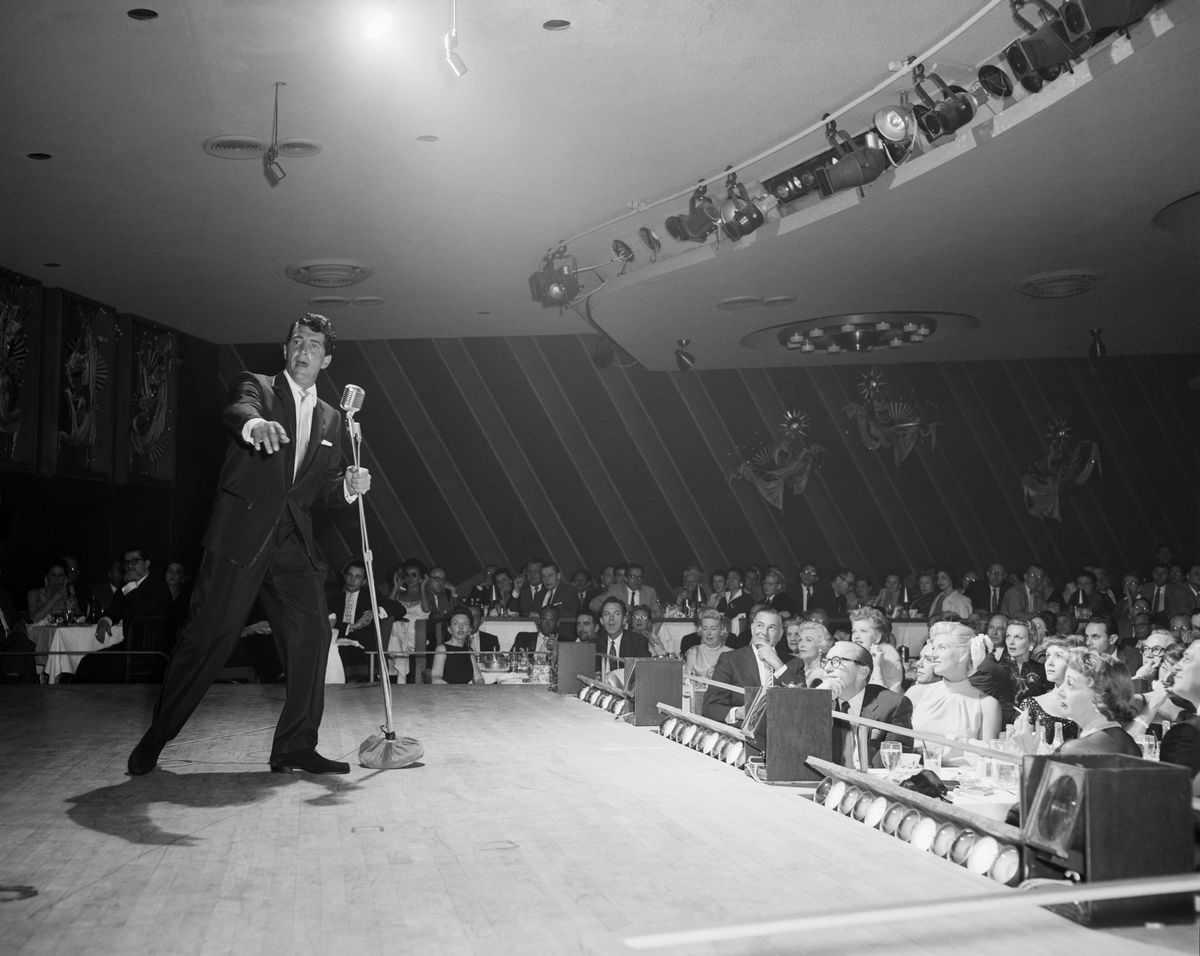 Slide 3 of 50: Dean Martin performs at the Sands in 1957. The Copa Room was the showroom for the hotel, and it was the stage for some of the greatest names in the entertainment industry.