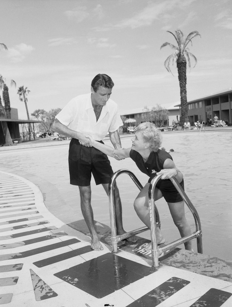 Slide 12 of 50: Actors Peter Lawford and Judy Holliday by the pool of the Sands in 1953. The two were costars in the romantic comedy It Should Happen to You.