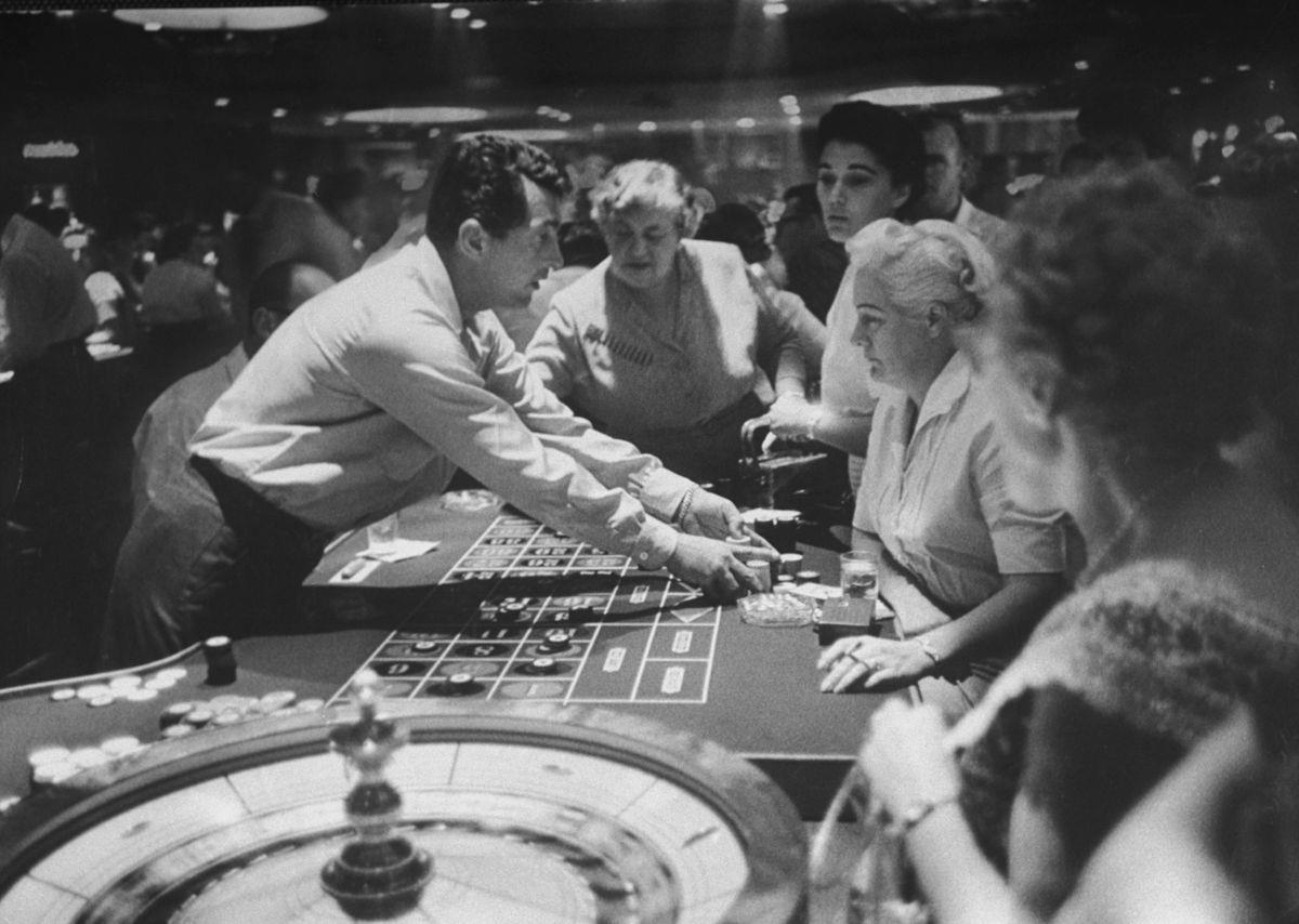 "Slide 26 of 50: Dean Martin deals at a casino in 1958. He was a member of the ""Rat Pack,"" which was made up of a group of entertainers that performed in Las Vegas at casinos."
