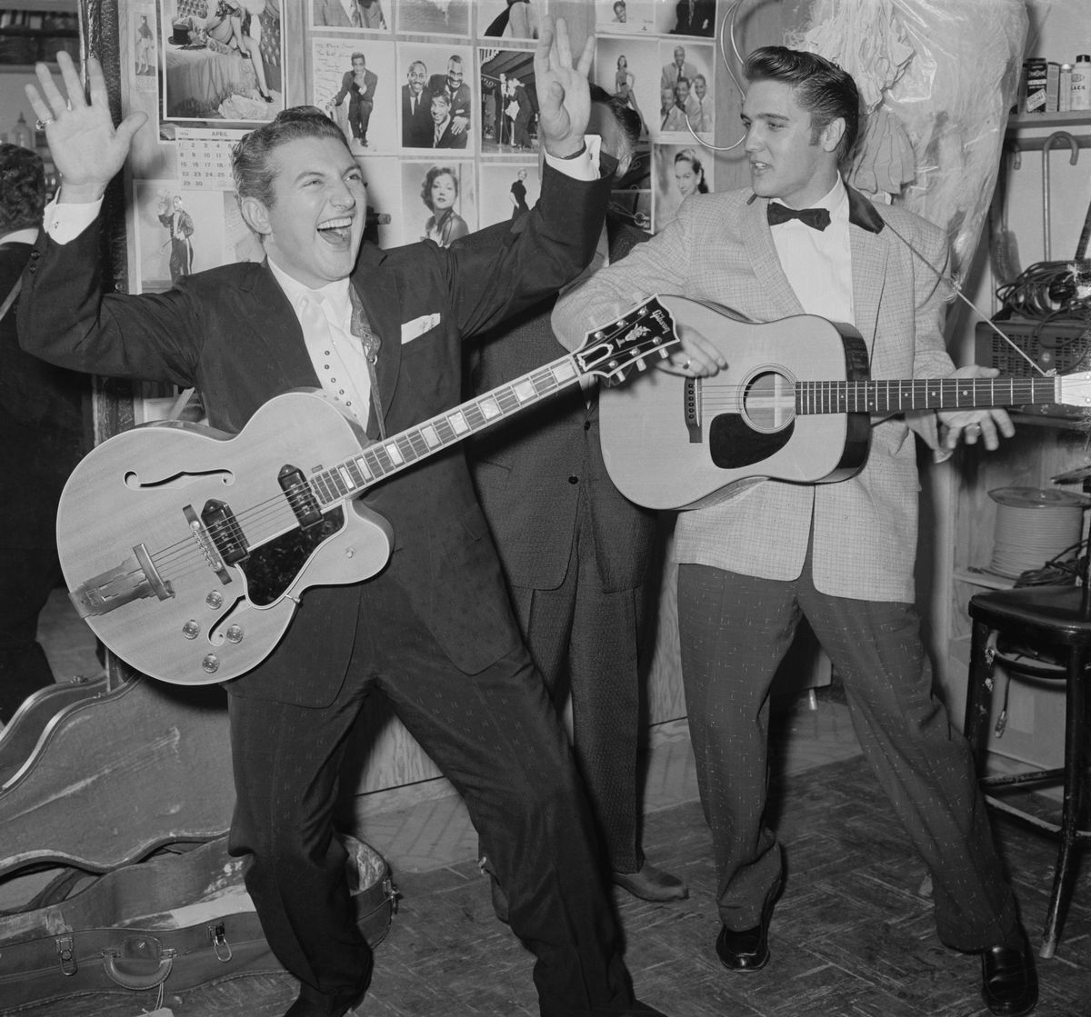 Slide 19 of 50: Liberace and Elvis Presley jam backstage at a night club in 1956. They first met when Liberace went to the Frontier to see Presley perform. Presley returned the favor and went to the Riviera to see Liberace's act.