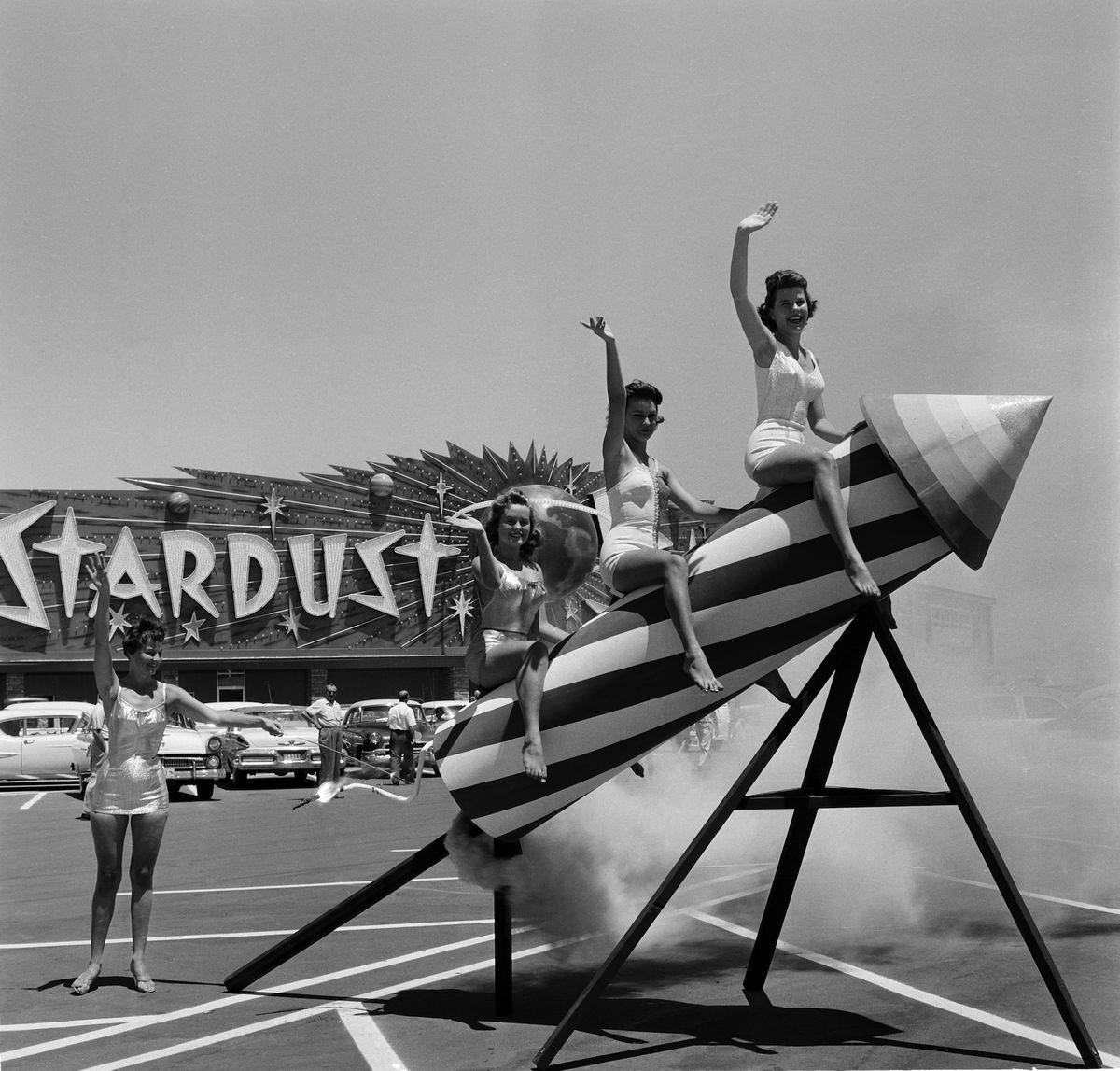 Slide 24 of 50:  Women sit and pose on a rocket outside the Stardust Resort and Casino in 1958. When the hotel opened, it had the largest casino and swimming pool in Nevada.