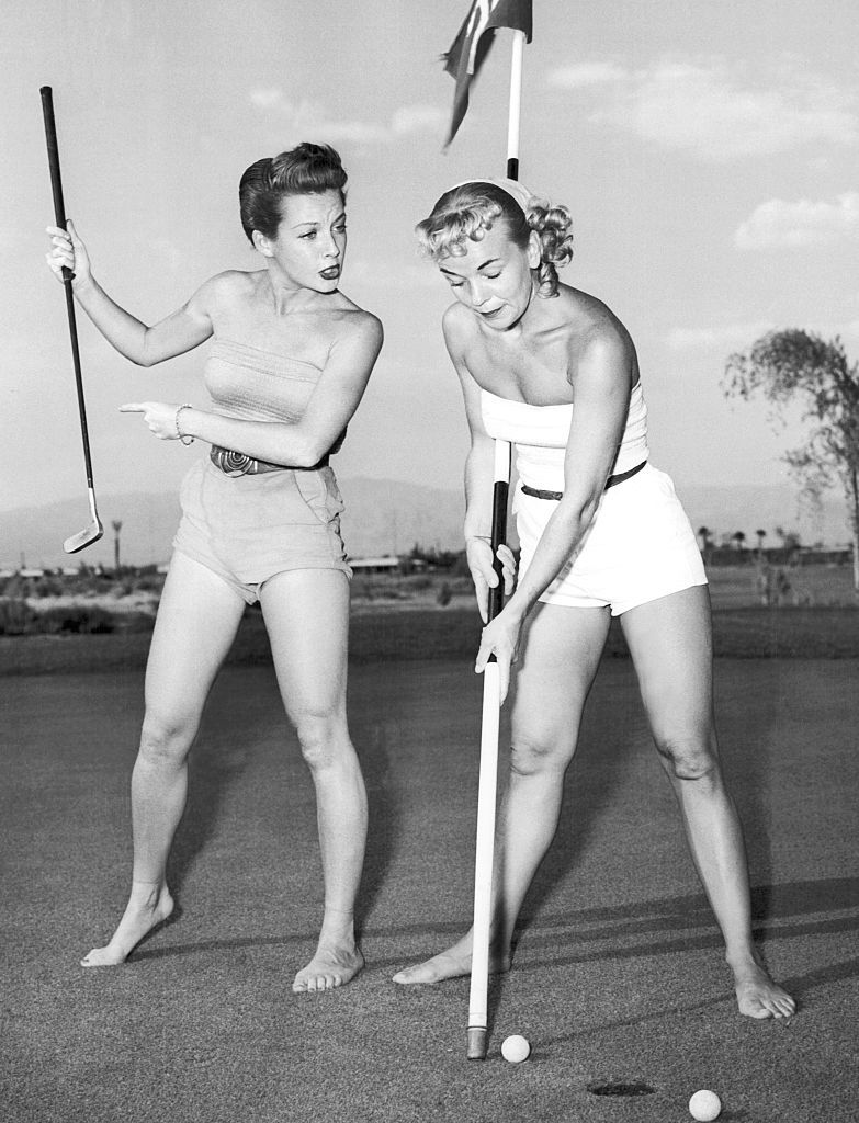 Slide 41 of 50: Showgirls Joy Skylar and Florence Walters practice their golf game in Las Vegas prior to a showgirl golf tournament held at the Desert Inn Country Club in 1953.