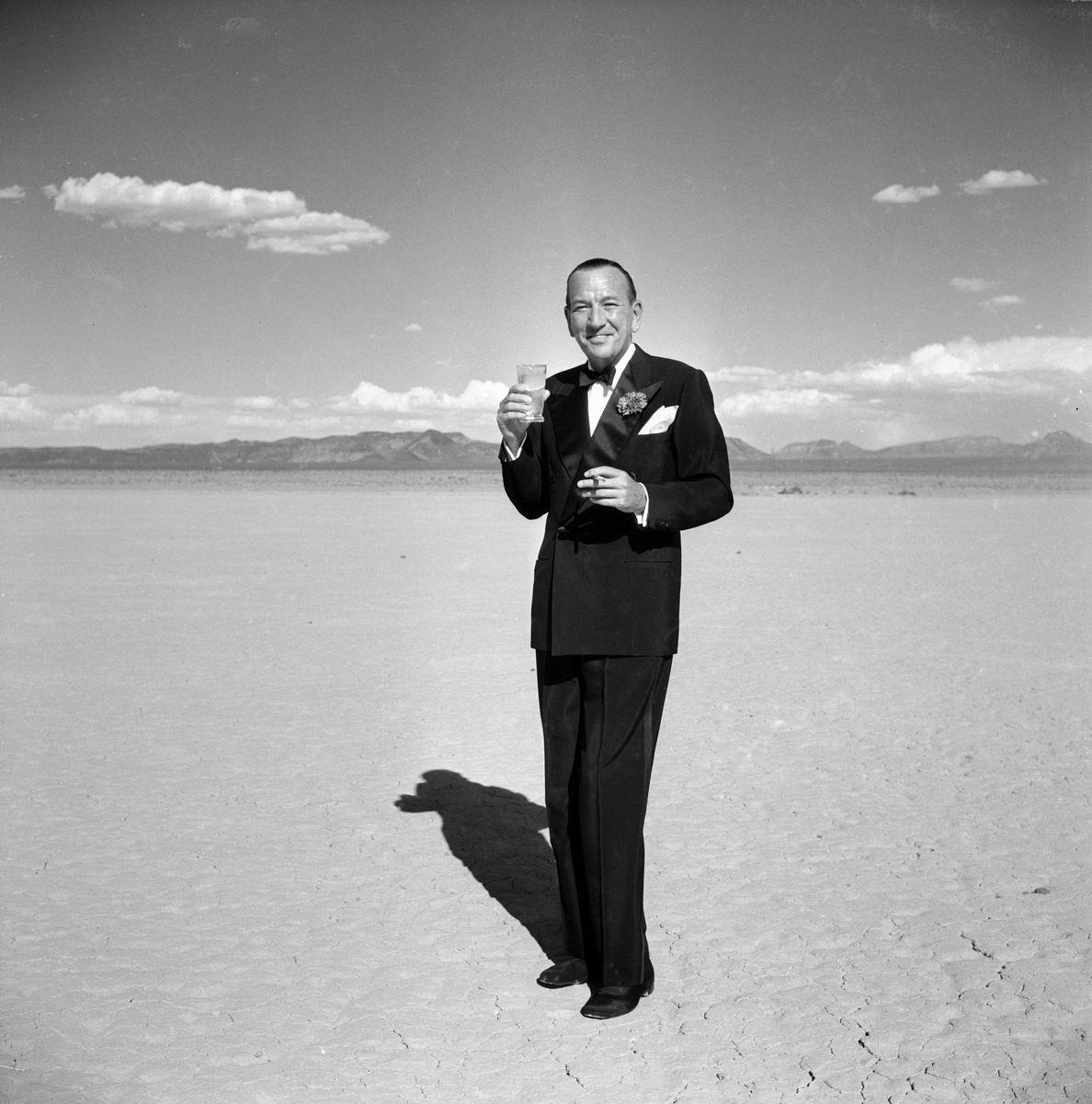 Slide 47 of 50: In a photo that sells the allure of the desert, actor Sir Noël Coward poses in a tuxedo with a cocktail and a cigarette in 1955.