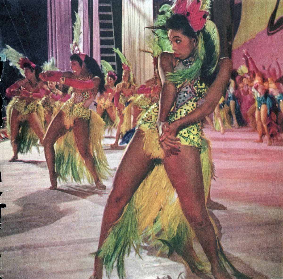Slide 48 of 50: Showgirls dressed in colorful sequins and feathered corsets perform at the Moulin Rouge in 1955.