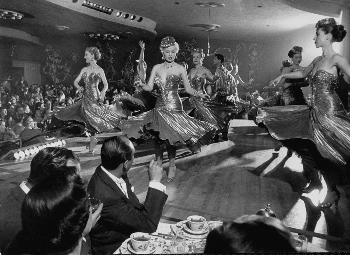 Slide 16 of 50: Showgirls dance on stage in 1952. The iconic Vegas showgirl first started in the 1950s and the idea came from Paris.