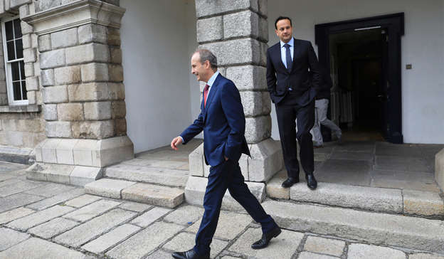 Leo Varadkar wearing a suit and tie walking on a sidewalk: Mr Martin is facing further disquiet within the ranks of his own party over the controversy. Pic: JULIEN BEHAL PHOTOGRAPHY.