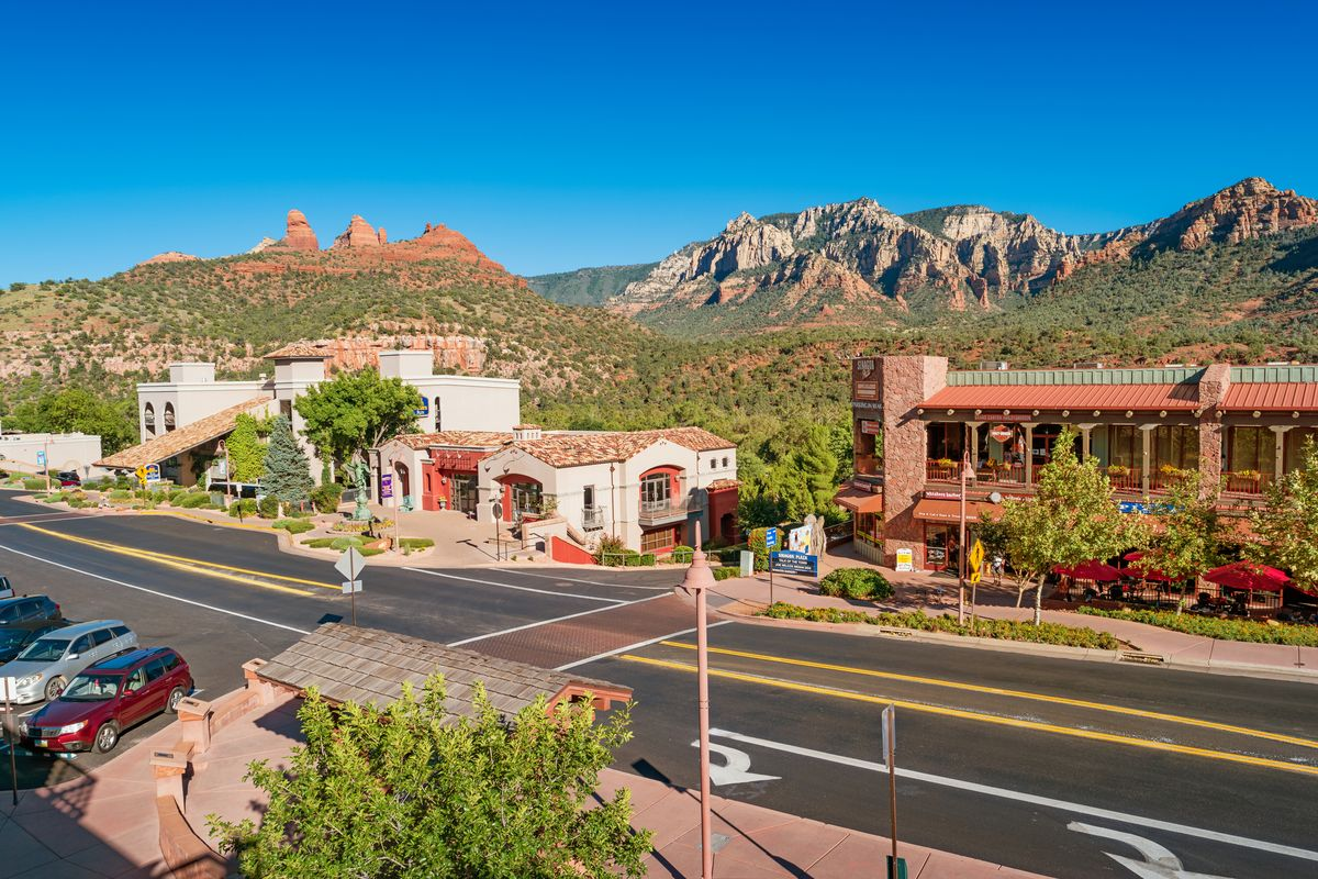 Slide 5 of 21: Although it's become a really popular spot, Sedona is still a desert town. Located near Flagstaff, it's surrounded by the famously beautiful red-rock buttes Arizona is known for, as well as steep canyon walls and pine forests. The mild climate makes it an ideal place to hike and explore nature. Uptown Sedona is an artist's paradise. If you're the hiking type, make sure to find some of the vortexes.