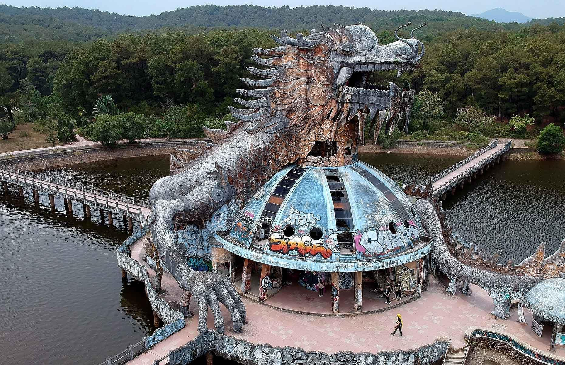 Slide 32 of 40: Perhaps the most intriguing structure in the park is this giant sculpture of a dragon, overlooking a lake. Urban explorers have even climbed inside, via a staircase located in the beast's body, to peer out from its gnashing teeth.