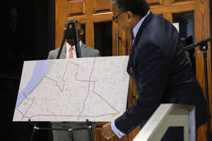 a man wearing a suit and tie: JW Gibson reveals a map of the area in South Memphis that the TIF will focus on, Thursday, Sept. 24, 2020, in Memphis, TN.