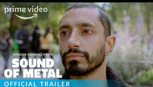 Riz Ahmed smiling for the camera: During a series of adrenaline-fueled one-night gigs, itinerant punk-metal drummer Ruben (Riz Ahmed) begins to experience intermittent hearing loss. When a specialist tells him his condition will rapidly worsen, he thinks his music career — and with it his life — is over. His bandmate and girlfriend Lou (Olivia Cooke) checks the recovering heroin addict into a secluded sober house for the deaf in hopes it will prevent a relapse and help him learn to adapt to his new situation. But after being welcomed into a community that accepts him just as he is, Ruben has to choose between his equilibrium and the drive to reclaim the life he once knew. Utilizing startling, innovative sound design techniques, director Darius Marder takes audiences inside Ruben's experience to vividly recreate his journey into a rarely examined world.  This trailer purposefully includes captions (just like the film itself) so that hearing and non-hearing audiences can experience Ruben's journey.  Sound of Metal arrives in select theaters November 20, and on Prime Video December 4 in the U.S. 