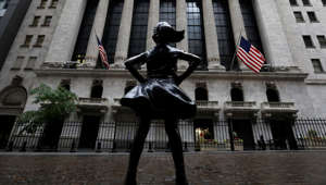 a statue of a person in front of a building: The Fearless Girl statue is seen outside the New York Stock Exchange (NYSE) in New York City, New York, U.S., June 11, 2020.