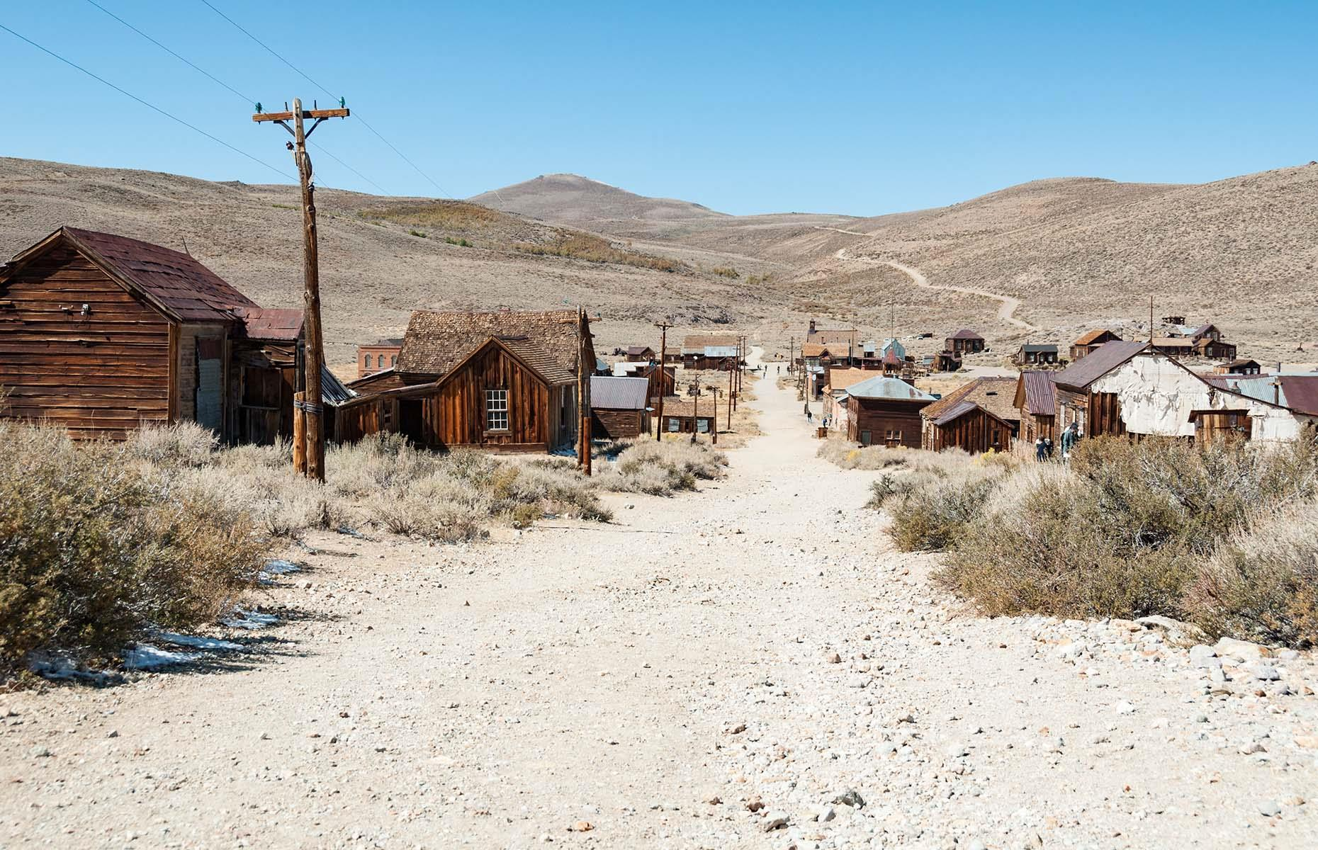 Slide 20 of 46: Perhaps the best-known Gold Rush ghost town in all of America, Bodie has attracted travelers and photographers for years. In its heyday, this California gold mining town had 10,000 inhabitants and 65 saloons, gambling halls, opium dens and brothels. The frequent outbreaks of violence and murders earned Bodie the dubious reputation as the most lawless mining camp in the far west.