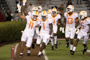 a group of football players on a field: Tennessee's Henry To'o To'o (11), Trevon Flowers (1), Deandre Johnson (13) and Kenneth George Jr. (5) celebrate an interception return for a touchdown against South Carolina during the first half of an NCAA college football game Saturday, Sept. 26, 2020, in Columbia, S.C.