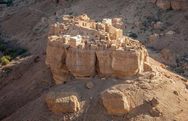 Slide 19 of 31: In the heart of Yemen's desert valley, known for its intensely hot and dry climate, lies the extraordinary little village of Haid Al-Jazil. This 500-year old settlement sits on a boulder which rises 350 feet (107m) above the ground, making it one of the most isolated yet strikingly beautiful places on Earth. Even more incredible is the fact that as recently as 2004, when the latest census was taken, 17 people still called Haid Al-Jazil their home.