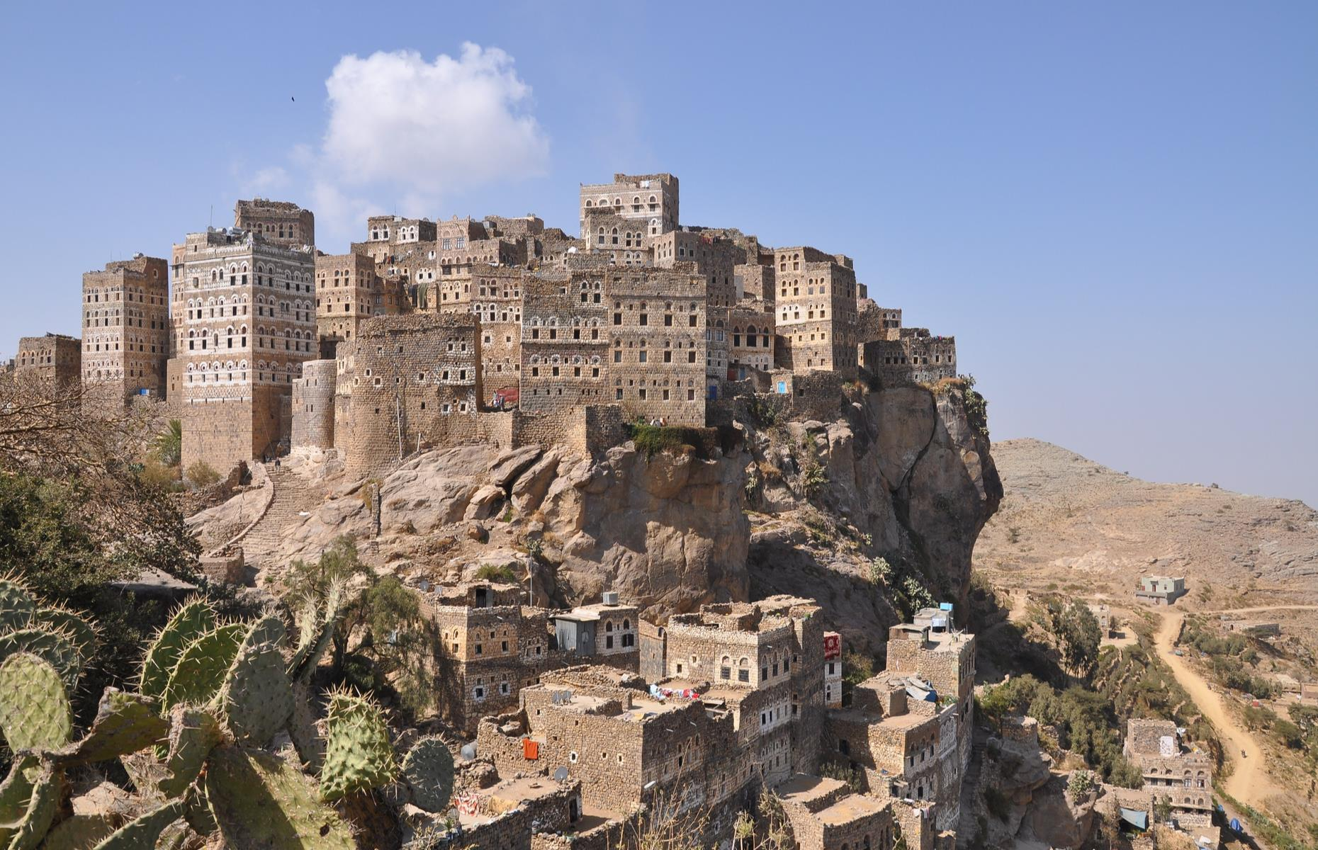 Slide 27 of 31: A cluster of towering houses built on an overhanging rocky crag in the Manakhah district of Yemen, Al-Hajjarah was founded in the 12th century and served as an important fortification during the Ottoman Empire. The mountain village's stone buildings merging almost imperceptibly with the cliffs below make for a mesmerizing sight.