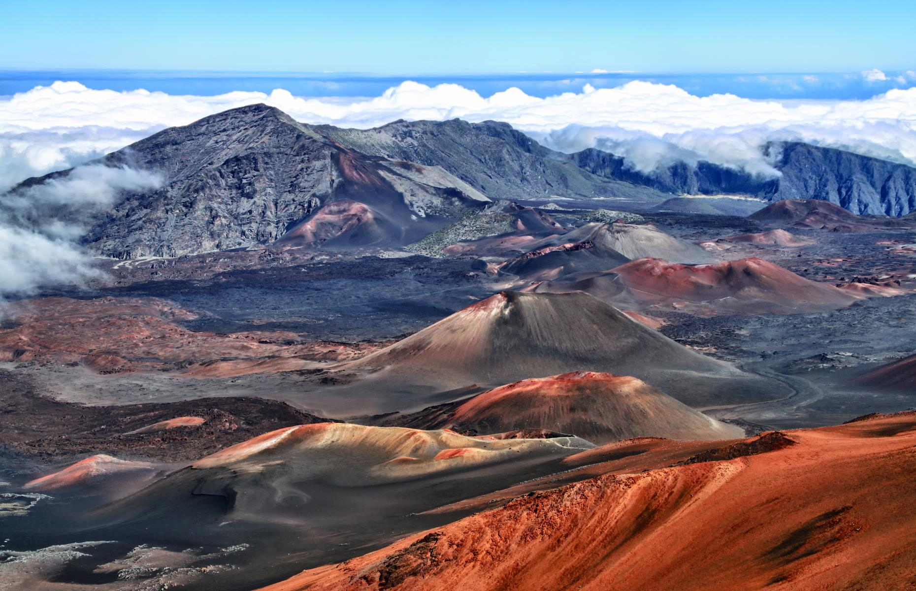 """Slide 25 of 41: This is about as close to the stars as you're likely to get. Haleakalā, the name ofthe dormant volcano within the park'slimits, means """"House of the Sun"""" in Hawaiian, and the locationis famed for its epic views of the sunrise. Nosing right up to the clouds, the Summit Area is the most otherworldly swathe of all: it's all rich cinder desert scattered with native shrubs, plus brighter than bright stars winking by night."""