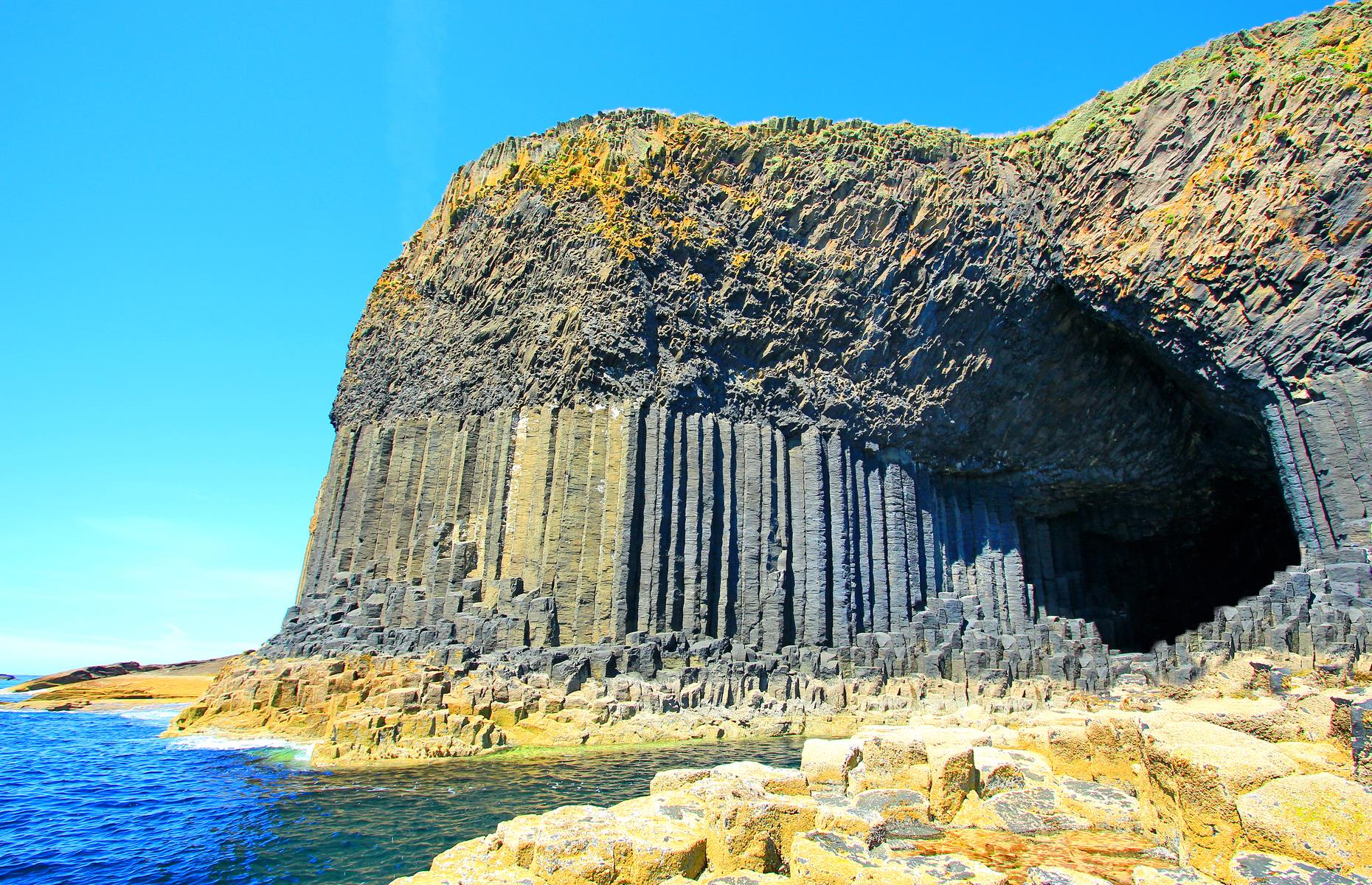 Slide 31 of 41: A volcanic wonder on the Isle of Staffa, Fingal's Cave is formed of neat, hexagonal, basalt columns that look like they've been carefully placed by hand. They're actually the work of Mother Nature, and the very same lava flow that carved out the famed Giant's Causeway across the water. Even so, plenty maintain that this striking sea cave and its Irish cousin were the work of giants.