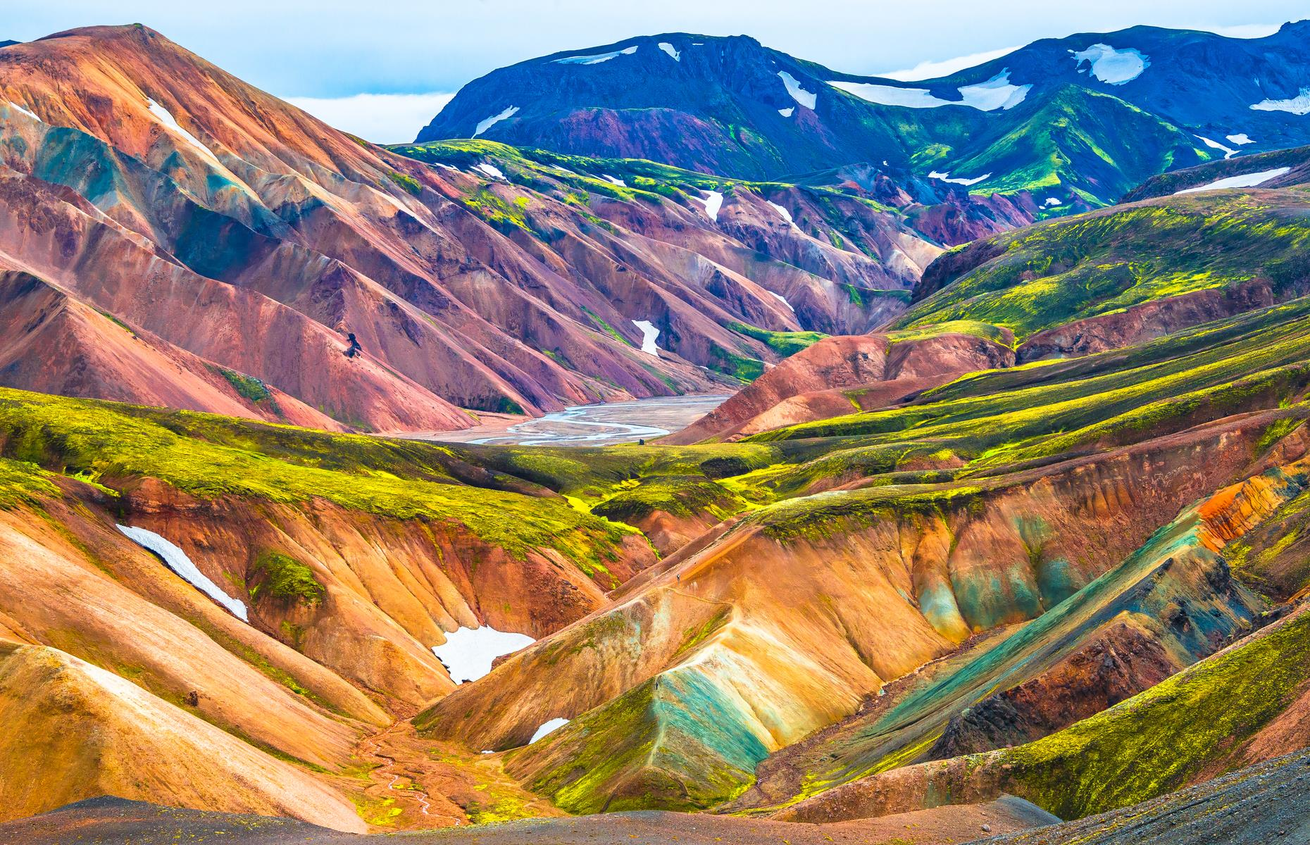 Slide 30 of 41: Deep in the Highlands of Iceland lies Landmannalaugar, a unique, undulating landscape made up of rhyolite crags, lava fields and natural hot springs. The region is favored by hikers who come in summer to admire the colorful mountains (made bright by geological deposits over centuries), and to keep watch for the trolls and elves that purportedly lurk amid the bluffs.