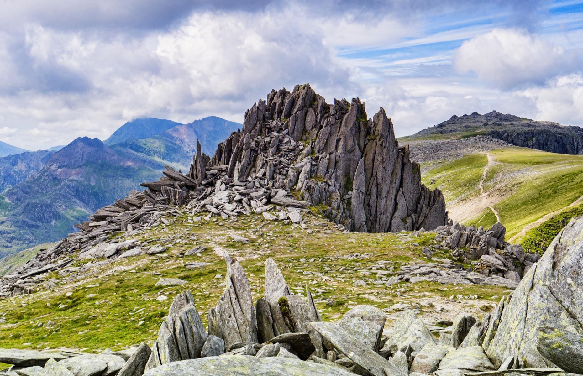 "Slide 26 of 41: A saw-toothed crown of Snowdonia's Glyderau range, Castell y Gwynt – meaning ""Castle of the Wind"" – soars to more than 3,000 feet (914m). Its jagged spires look a little like a brooding fairy-tale fortress, so it's no surprise that the peak featured in Disney's Dragonslayer, a 1980s movie with wizards, dragons and plenty of glimpses of the dramatic North Wales landscape. Discover more places you won't believe are in the UK."
