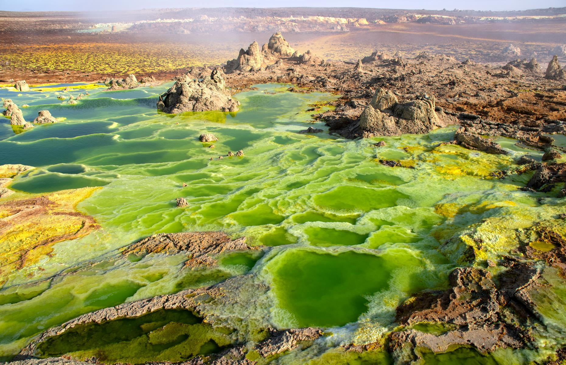 Slide 24 of 41: Ethiopia's answer to Yellowstone's Grand Prismatic Spring, Dallol volcano sits in the far northern reaches of the country. The geothermal area is a green and yellow land of sulfur ponds, geysers and salt plains, with the volcano itself only springing up in 1926. This pocket of Ethiopia is notably one of the lowest places on the planet too.