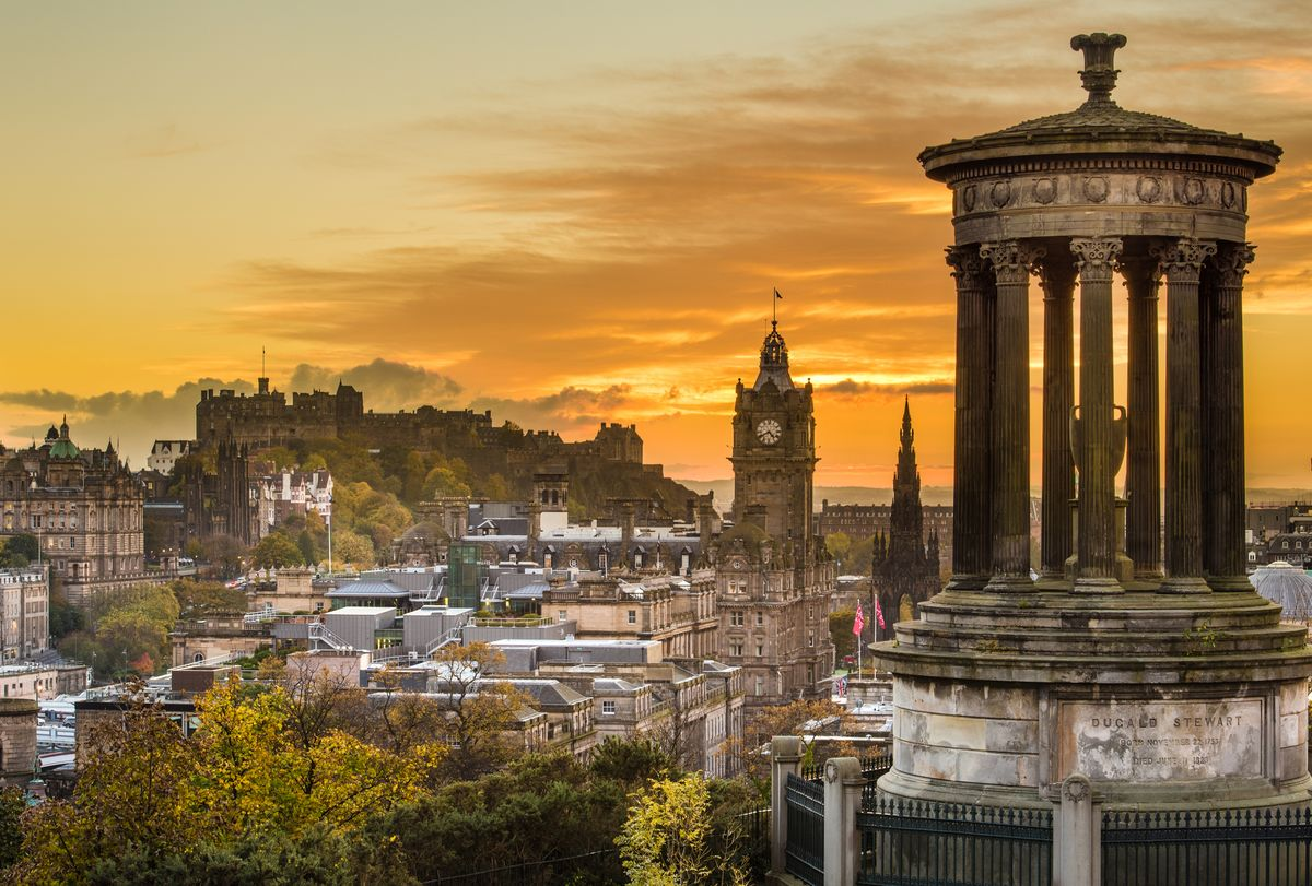 Slide 6 of 33: An autumn sunset in the capital city of Edinburgh, with the Edinburgh Castle and Balmoral Hotel Clock Tower in view.