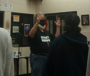a man standing in front of a mirror posing for the camera: Powell High School choir director Jim Kennedy doesn't let a mask ruin his instructions.