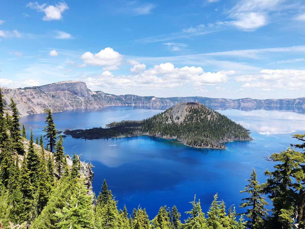 Slide 38 of 51: Crater Lake National Park Nature can be kinda wild, and that's on display here. A volcano erupted almost 8,000 years ago and then caved in on itself, creating this beautiful, deep lake that is filled by rain and snow. Its sparkling color is magnificent in the sun.