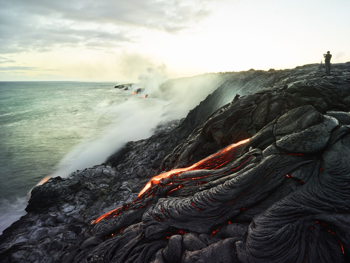 Slide 12 of 51: Hawai'i Volcanoes Normally you'd run far away from an active volcano, but here you can sometimes see the lava slowly flow like a river into the ocean. When the lava isn't flowing, you can still see the amazing craters and unusual terrain that they've left in their wake.