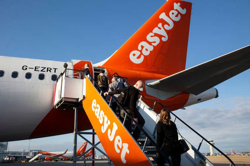 a large air plane on a runway at an airport: An easyJet plane