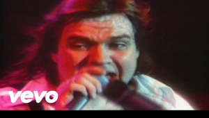 "a blurry photo of a man: Watch the official music video for ""Paradise By The Dashboard Light"" by Meat Loaf Listen to Meat Loaf: https://Meatloaf.lnk.to/listenYD  Subscribe to the official Meat Loaf YouTube channel: https://Meatloaf.lnk.to/subscribeYD  Watch more Meat Loaf videos: https://Meatloaf.lnk.to/listenYC/youtube  Follow Meat Loaf: Facebook: https://Meatloaf.lnk.to/followFI Twitter: https://Meatloaf.lnk.to/followTI Website: https://Meatloaf.lnk.to/followWI Spotify: https://Meatloaf.lnk.to/followSI YouTube: https://Meatloaf.lnk.to/subscribeYD  Lyrics:  I remember every little thing As if it happened only yesterday Parking by the lake And there was not another car in sight And I never had a girl Looking any better than you did And all the kids at school They were wishing they were me that night  And now our bodies are, oh, so close and tight It never felt so good, it never felt so right And we're glowing like the metal on the edge of a knife Glowing like the metal on the edge of a knife C'mon, hold on tight C'mon, hold on tight  Though it's cold and lonely in the deep dark night I can see paradise by the dashboard light  #MeatLoaf #ParadiseByTheDashboardLight #OfficialMusicVideo"