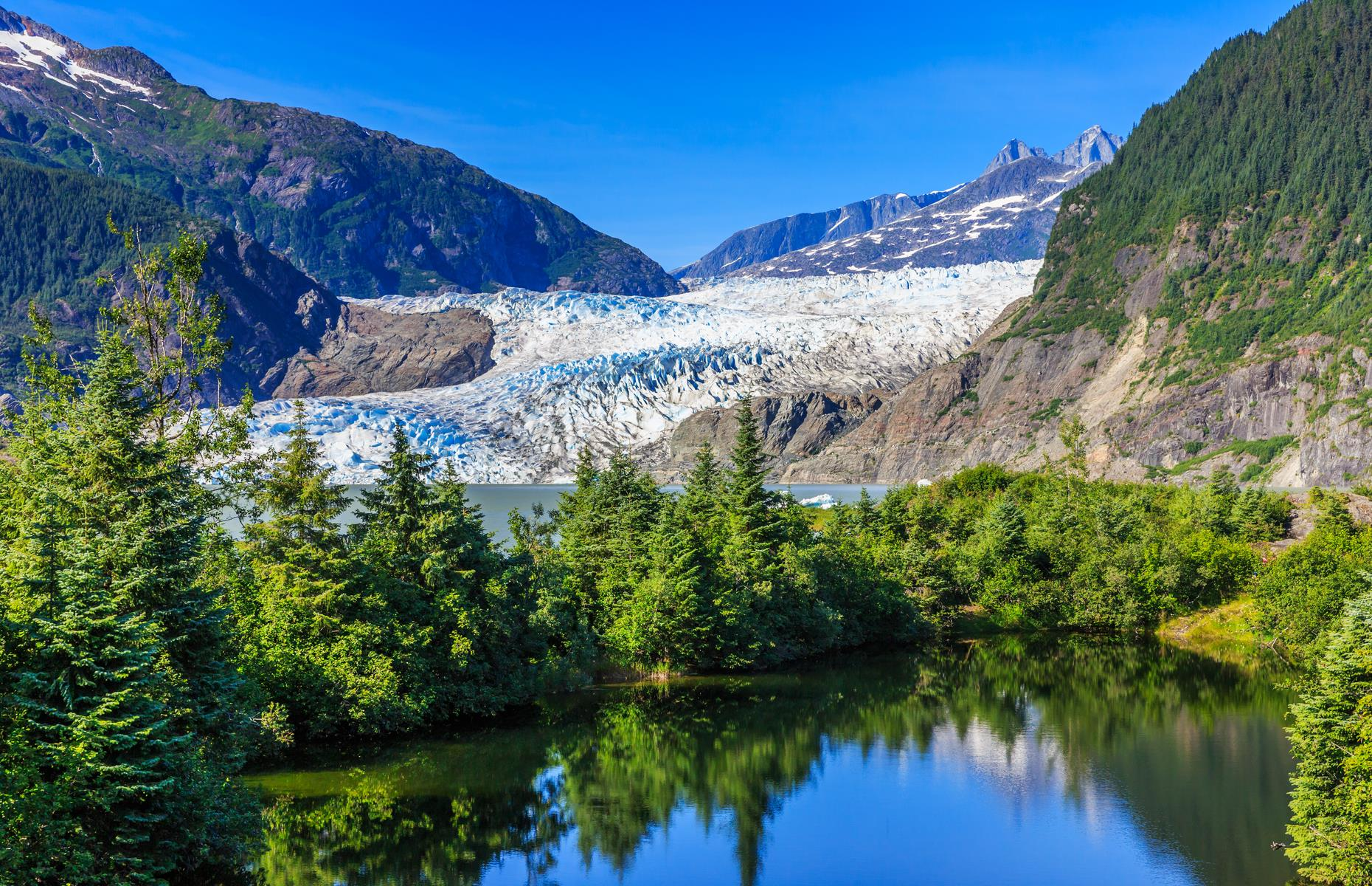 Slide 12 of 35: One of Alaska's most accessible glaciers, Mendenhall Glacier is located a mere 13 miles (21km) from the town of Juneau and can be reached by car, on foot, by air, or by boat. Part of the 1,500 square mile (3,900sq km) Juneau Icefield, the glacier has been retreating since the Little Ice Age between the 16th and 19th centuries. The glacier is accessible all year but May to October, when the weather is warmest, is the most popular time to visit (when COVID-19 restrictions allow).