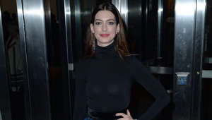 Anne Hathaway standing in front of a door