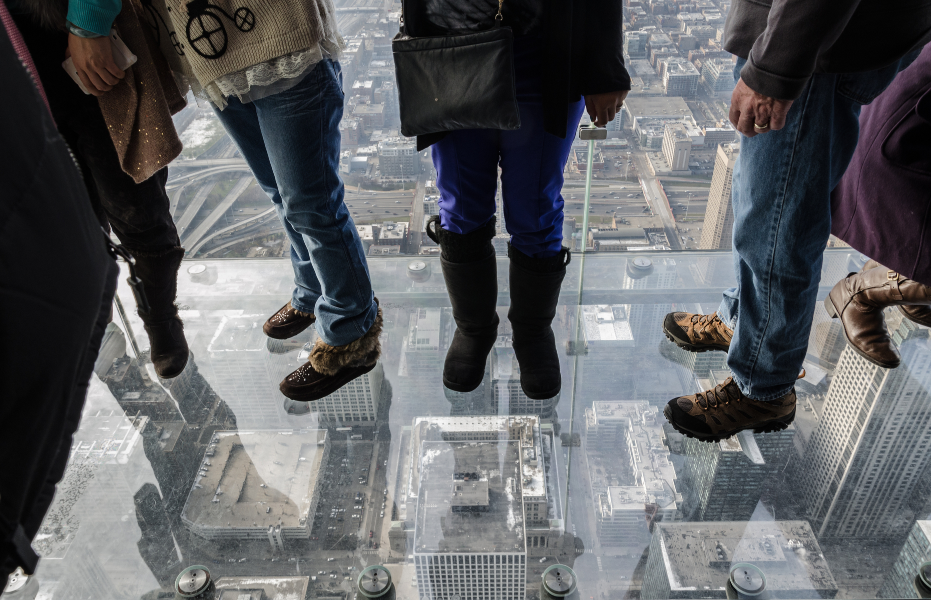Slide 10 of 16: Chicago's famous Willis Tower invites visitors to experience The Ledge, a balcony made of floor-to-ceiling glass. On a clear day, you can see as far as 80 kilometres (50 miles)—a view that spans four states! The Ledge is on the 103rd floor at a height of 412 metres (1,352 feet), and it's a popular spot for marriage proposals.