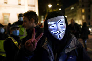 A masked person gestures as protestors from the Million Mask March and anti lockdown protesters demonstrate, amid the coronavirus (COVID-19) outbreak in London, Britain November 5, 2020.  REUTERS/Henry Nicholls