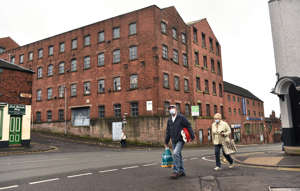 LEEK, ENGLAND - NOVEMBER 11: People are seen walking past an old mill with their shopping in the Market Town of Leek on November 11, 2020 in Leek, England. The United Kingdom will continue to impose lockdown measures until December 2 in an attempt to curb transmissions of the coronavirus (COVID-19). (Photo by Nathan Stirk/Getty Images)