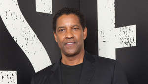 Denzel Washington holding a sign posing for the camera