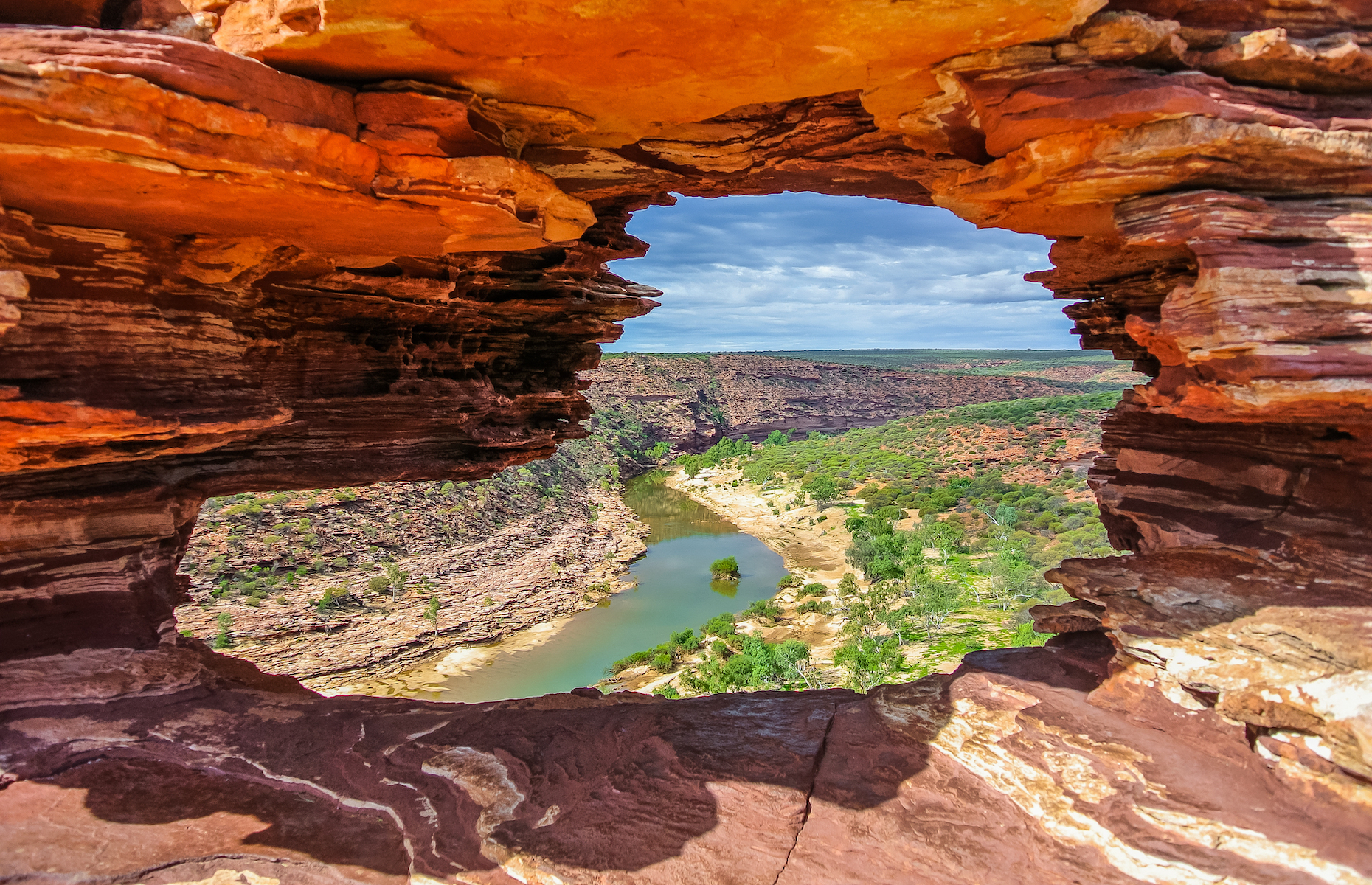 Slide 4 of 21: The Murchison River, second-longest river in Western Australia, flows past sandstone cliffs and straight out to the Indian Ocean. Peek through Nature's Window, formed from layers of Tumblagooda Sandstone, to see the beautiful coastal gorges of Kalbarri National Park.