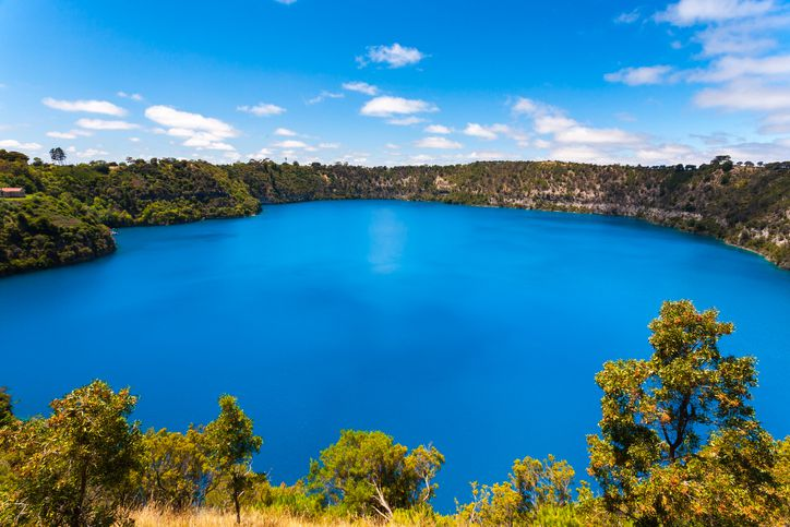 Slide 31 of 52: This lake, which formed in the crater of an extinct volcano, turns a brilliant blue during Australia's summer months. During the winter, its color is more muted, and scientists are still not sure why.